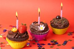 Miniature chocolate cupcakes with candle stock image