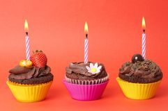 Miniature chocolate cupcakes with candles Royalty Free Stock Photography