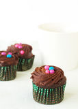 Miniature chocolate cupcakes and coffee. Miniature decorated chocolate cupcakes and coffee on white background Royalty Free Stock Images