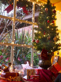 Miniature Christmas tree in window. Christmas lights and decoration all over Royalty Free Stock Images