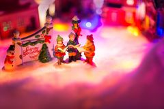 Kid choir singing next to holiday greeting sign with snowy christmas village in the background. seasons greeting festive concept. Miniature festive red Stock Images