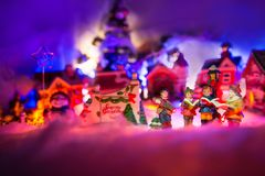 Kid gospel choir singing next to Seasons greeting sign with snowman and christmas village in the background. Fairytale miniature. Miniature festive red stock photography