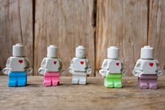 Miniature clay doll standing together on wooden surface stock photos