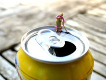 Miniature cleaning lady sweeping drops on top of soda can Stock Photos