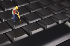 Miniature Construction Worker On Top Of A Computer Keyboard Royalty Free Stock Photos
