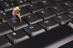 Miniature Construction Worker On Top Of A Computer Keyboard Royalty Free Stock Photography