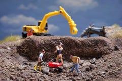 MiniatureContruction arbetare som arbetar lyftande stenen genom att använda skyffeln royaltyfria bilder