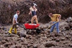 MiniatureContruction pracownicy pracuje podnośną kamienną używa łopatę obraz stock