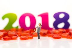 Miniature couple, couple hugged each other. Surrounded by red crystal hearts, background the New Year in 2018. Used in the Valentine`s day concept Royalty Free Stock Images