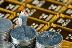 Miniature couple figure standing on stack of coins with shiny go. Ld bars as business or financial investment and wealth concept Stock Images