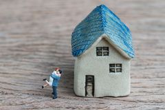 Miniature couple, happiness husband and wife with ceramic house. Using as success marriage life or mortgage concept Royalty Free Stock Photography