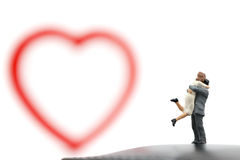 Miniature couple hugging and red heart on white background Stock Photography