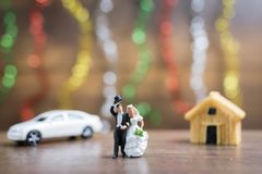 Miniature couple hugging on wooden floor with colorful bokeh bac Stock Image