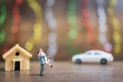 Miniature couple hugging on wooden floor with colorful bokeh bac Royalty Free Stock Photos