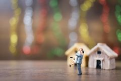 Miniature couple hugging on wooden floor with colorful bokeh bac Royalty Free Stock Image