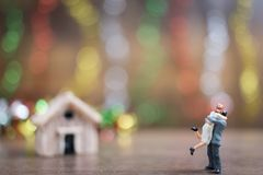 Miniature couple hugging on wooden floor with colorful bokeh bac Stock Photos