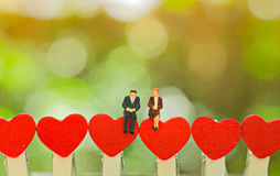 Miniature couple sitting on red heart , valentine concept.  Stock Image