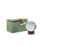 Miniature, crystal ball on wooden stand with Oriental themed case. Miniature, crystal ball on a stand made from cherry wood. Next to it is a hand-embroidered Royalty Free Stock Image