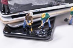 Miniature d'ouvrier chargé de l'entretien réparant le téléphone image libre de droits