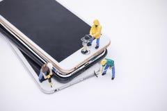 Miniature d'ouvrier chargé de l'entretien réparant le téléphone images libres de droits