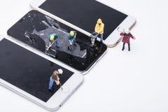 Miniature d'ouvrier chargé de l'entretien réparant le téléphone photo libre de droits