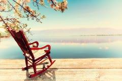 Miniature d'une chaise de basculage devant une lagune, symbolisant r image libre de droits