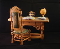 Miniature desk. A miniature desk with an armchair, books and a globe Stock Photo