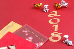 Miniature dogs with chinese new year decorations - series 4. Chinese new year decorations for year 2018 on red surface royalty free stock photography