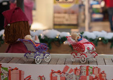 Miniature doll buggies  on conveyor belt in shopping center Stock Image
