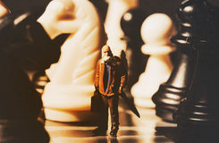 Miniature doll and chess vintage toned photo. Old traveler on chessboard. Royalty Free Stock Photo