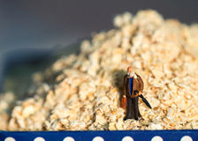 Miniature doll traveler and oatmeal in metallic can. Old person diet. Health care concept image. Aged man traveling over cereal mountain. Healthy breakfast Stock Photography