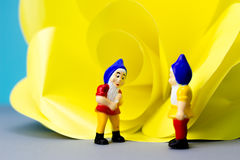 Miniature dwarves with giant flower. On blue background Royalty Free Stock Photos