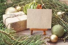 Miniature easel with blank card, gift box, pine branches and Chr Royalty Free Stock Photo