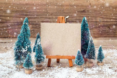 Miniature easel with blank card and miniature firs. Holiday card Stock Images