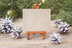 Miniature easel with blank card, pine branches and Christmas dec Royalty Free Stock Photos