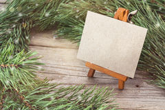 Miniature easel with blank card and pine branches. Stock Photos