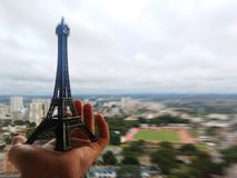 Miniature Eiffel Tower in a person`s hand against the horizon stock photos