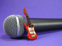 A miniature electric guitar propped up on a dynamic microphone. A red miniature electric guitar propped up on a dynamic handheld vocal microphone. Purple stock images