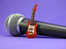 A miniature electric guitar propped up on a dynamic microphone stock images