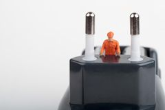Miniature of electrician on a plugin Royalty Free Stock Photos