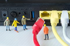Miniature engineer team try to connect ethernet cables to port Royalty Free Stock Photos