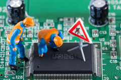Miniature engineers fixing error on chip Stock Photos