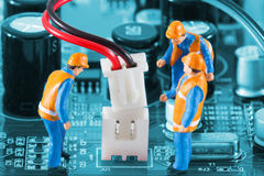 Miniature engineers fixing wire connector. Of circuit board. Computer repair concept. Close-up view Royalty Free Stock Photography