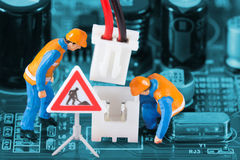 Miniature engineers fixing wire connector. On circuit board. Computer repair concept. Close-up view stock photography