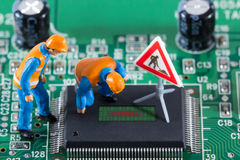 Miniature engineers looking at code on chip. Of circuit board. Computer repair concept. Close-up view royalty free stock photos
