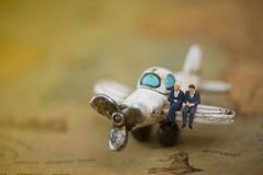 Miniature et avions avec le worldmap utilisant comme le fond Concentré Photo stock