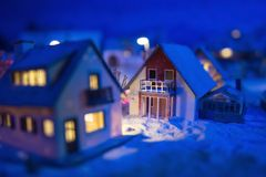Miniature European village during winter. Miniature houses in European village with snow at night with light up decoration. Christmas winter model for holiday stock photography
