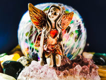 Miniature fairy Sitting on an Amethyst. Miniature fairy with red love heart sitting on Amethyst stone surrounded by gem stones with blue background Stock Photo