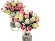 Photo Miniature fake Paper flowers in glass jar on white background. Dollhouse miniature, paper toy. Bouquet of pink and yellow ro royalty free stock photography