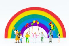 Miniature family: Children holding balloon with rainbow for background. Image use for international children`s day.  royalty free stock image